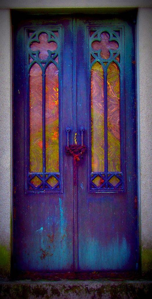 Description: C'est une porte en bois. Le bas et le  haut et turquoise, ensuite se dégrade en violet au centre de la porte. Il y a une corde rose qui attache les deux poignées de porte ensemble. Les fenêtres sont peinturer en rose et en jaune.  Appréciation: J'aime cette porte, car elle est colorer et architecturale.