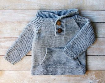 This sweater will fit babies and toddlers 12 to 18 months old.    Hand knitted from denim blue and soft green 100% wool yarn, this polo neck