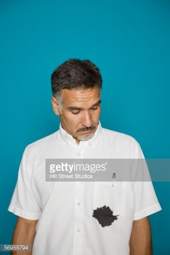 Stock Photo : Man looking at ink stain on shirt