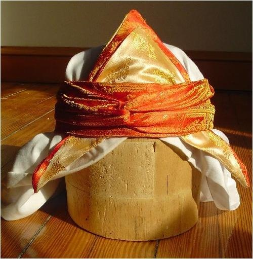 NapkinHat | Persian woman's headdress, with an orange brocade fillet, yellow and orange scarf folded in half, and white veil… undated  This type of female´s headdress is seen in many16th century Persian-Islamic Manuscripts llustration, sometimeswith long veils and other head ornaments.Middle eastern garb