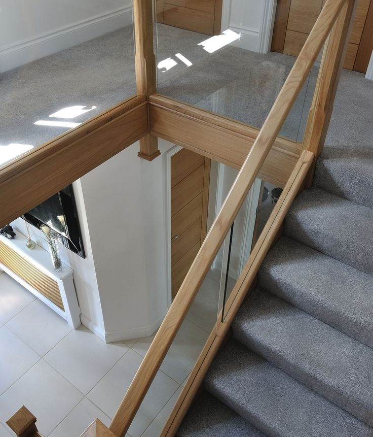 We used a modern mix of glass and natural oak with carpeted treads that sweep around the first-floor landing. This allowed us to create a contemporary style staircase with half landing. To add to the modern finish, glass is inset into the wooden staircase frame for a streamlined look. An alternative to using more traditional spindles. If you're looking for something similar, contact us on 02920 529 797 for a quote today. Covering England, Wales and the Channel Islands.