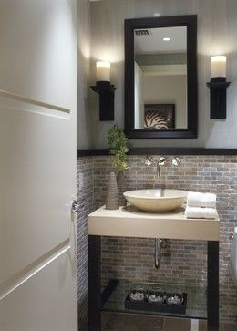 Spa-like Powder Room with stone top vanity with vessel sink and glass lower shelf, wall mounted faucet with cross handles in polished chrome finish, candle style sconces, framed mirror, travertine floors, mosaic stone wainscot in mini brick pattern, and custom door