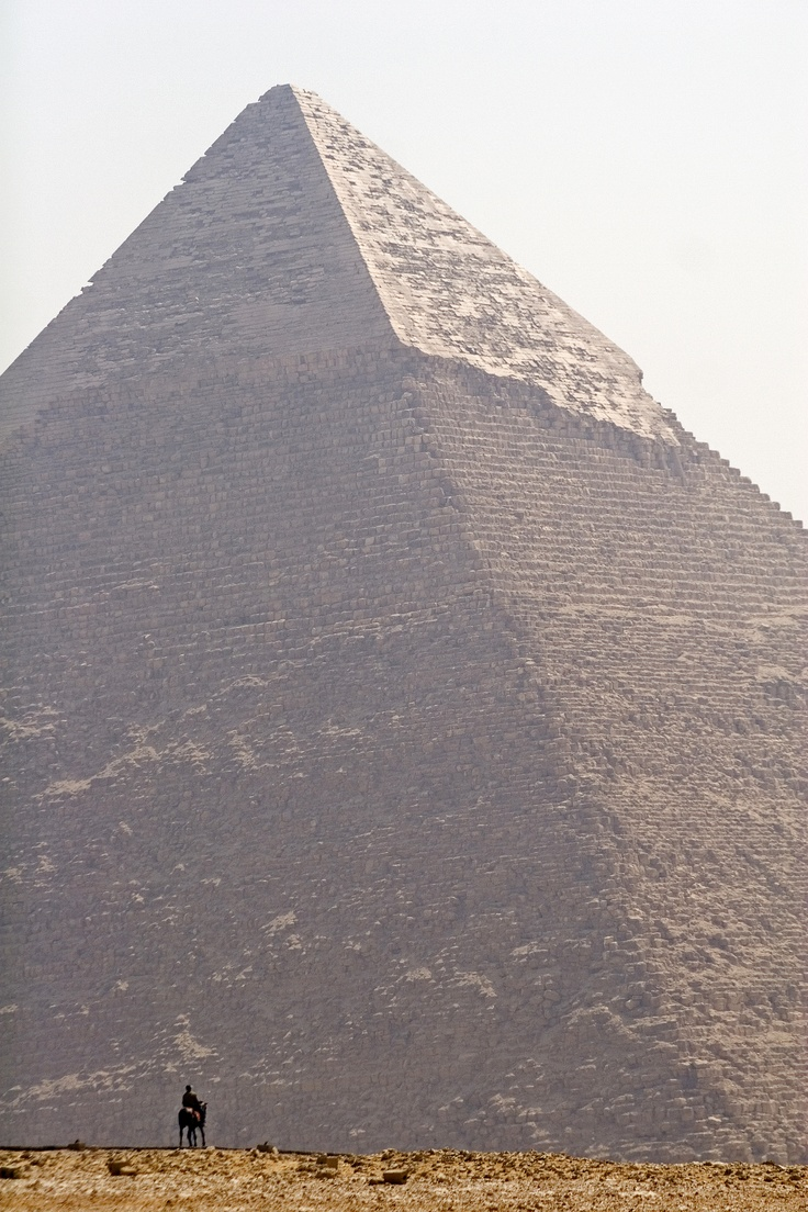 Pyramid of Kafre, the only pyramid to reatin some of its original limestone casing blocks. The small figure in the foreground gives perspective on the immensity of the size of these monuments.