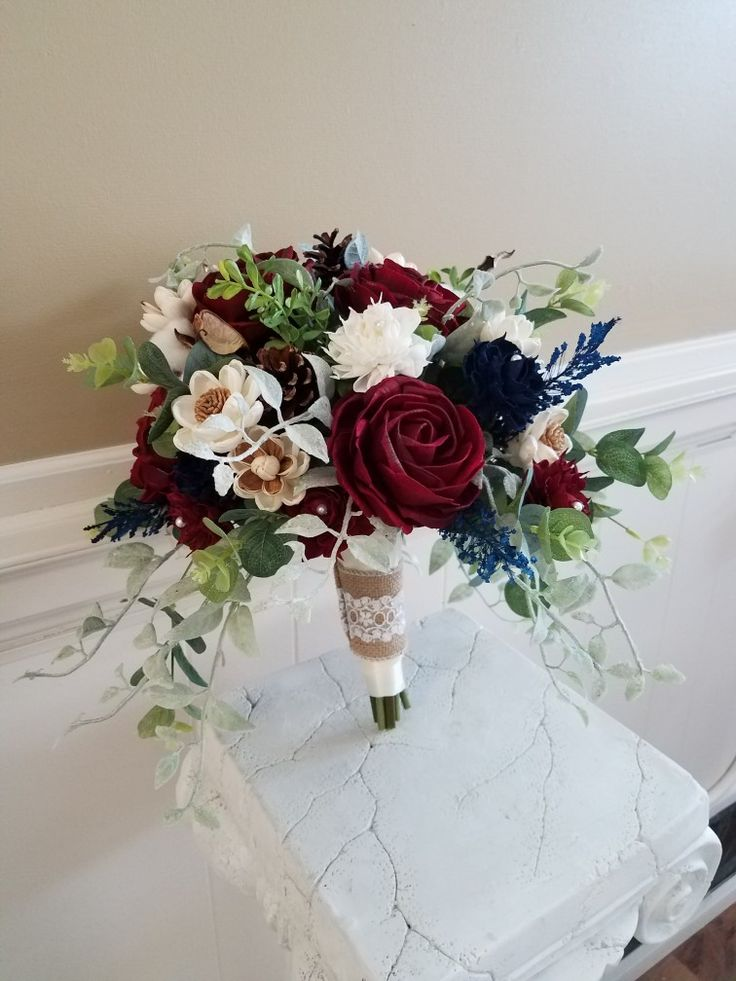 Silk and Sola Wood flowers bouquet in burgundy, Navy and Ivory. Beautiful natural pinecones are nestled in the bouquet. By Bride & Bloom, Gladwin, MI 48624 Facebook.com/thebrideandbloom We ship!