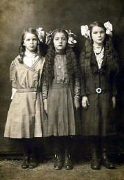 Three school girls with big hair bows circa 1890. The middle girl wears a locket and the girl on the right wears beads and a buckle on her belt.
