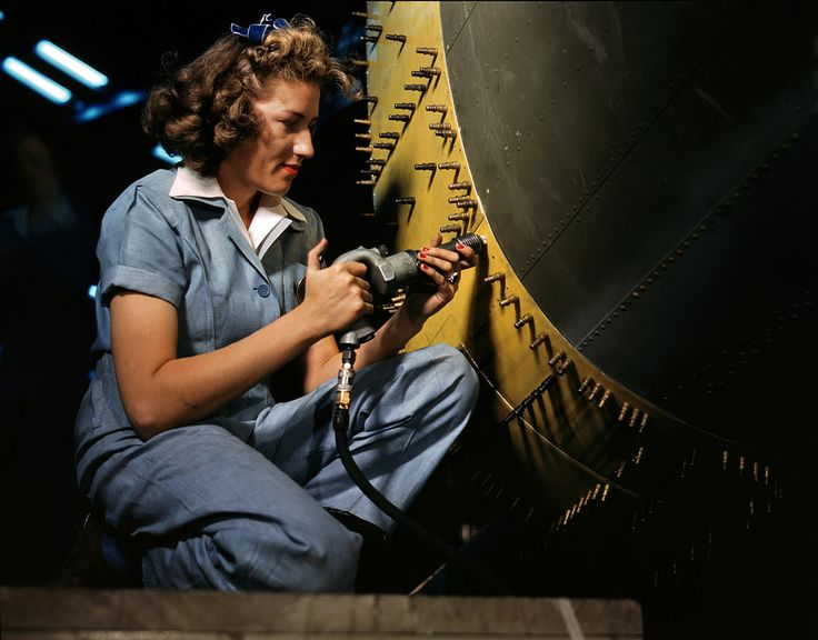 October 1942. Riveter at work on a bomber at the Consolidated Aircraft factory in Fort Worth. 4×5 Kodachrome transparency by Howard Hollem.