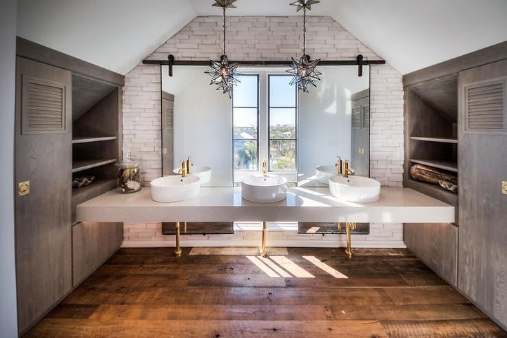 Shared kids' bathroom features a white quartz floating sink vanity topped with three overmount bowl sinks and brass faucets illuminated by two Moravian Star Pendants placed before mirrored sliding barn doors flanked by gray oak built-in cabinets adorned with vintage brass hardware.