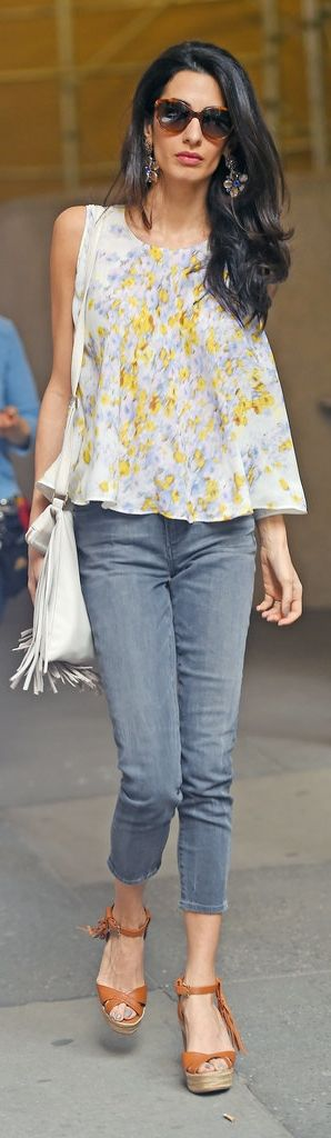 Amal Clooney looked like a boho goddess wearing a Giambattista Valli trapeze top, Dolce & Gabbana floral earrings, a fringe B-Low the belt bag, Prada sunglasses, cropped denim, and Valentino leather wedges.