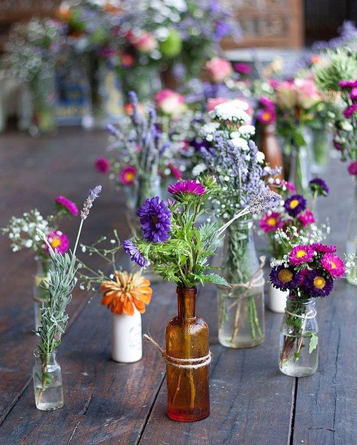 Kleurrijke bloemendecoratie in kleine Galsvasen voor zomerhuwelijk …