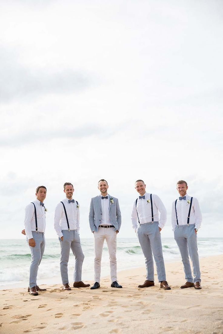 The groom and his groomsmen in grey and white complete with bowties and suspenders // Francois and Karis both hail from the fashion industry, so you can imagine the level of attention they paid to the design of their wedding at Aleenta Phuket Resort & Spa on the pristine Natai Beach. At the top of the couple's wish list was something unconventional and nature-inspired. The Wedding Bliss Thailand's palette of calming sea and froth colours, combined with unique flowers, were a perfect match fo