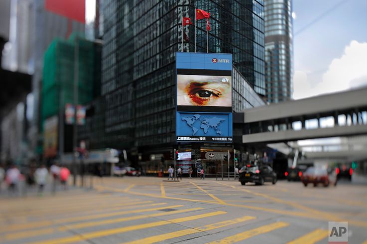In this June 23, 2017, photo made with a tilt-shift lens, a Chinese national flag and a Hong Kong flag fly above the central business district in Hong Kong. Two decades since Beijing took control of Hong Kong, China's rising influence – and Britain's waning profile – are impossible to ignore. (AP Photo/Vincent Yu)
