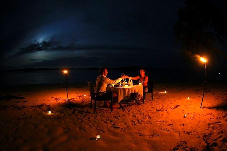 A recent couple at Resort Latitude Zero enjoying a romantic candle lit beach dinner. .