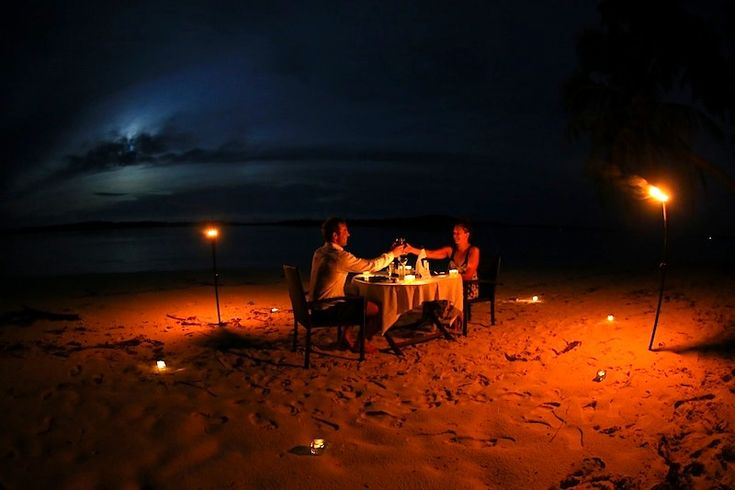A recent couple at Resort Latitude Zero enjoying a romantic candle lit beach dinner. .