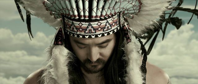 """Producer/DJ Steve Aoki wears it at the beginning and end of this video for """"Cudi the Kid (ft. Travis Barker and Kid Cudi)""""—he probably thinks the cultural mashup of a Japanese guy in a feather headdress looks cool. Not as cool as the burning clowns and psychotic nuns we see later in the clip, but still, not bad. Sacred regalia can't really compete with burning clowns, but then, what can?"""