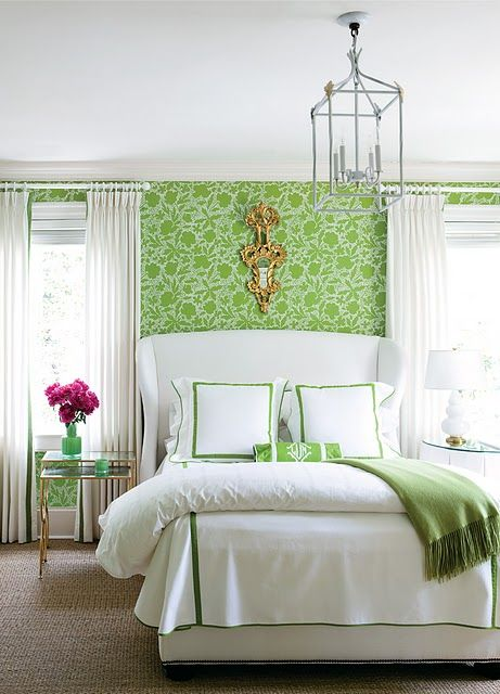 Margaret Bosbyshell - white & apple green bedroom design with apple green floral wallpaper, white wingback bed with white & green bedding, brass mirrored nesting tables nightstands, apple green blanket, white curtains, sisal rug and white lamp.