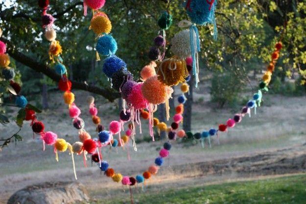 Decorazioni+colorate+per+Carnevale - Pon-pon+di+colori+diversi+uniti+gli+uni+agli+altri+da+un+filo+per+delle+decorazioni+colorate+perfette+per+il+giardino.