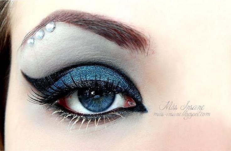 A trio of crystals enhances dramatic blue and black winged eye shadow.