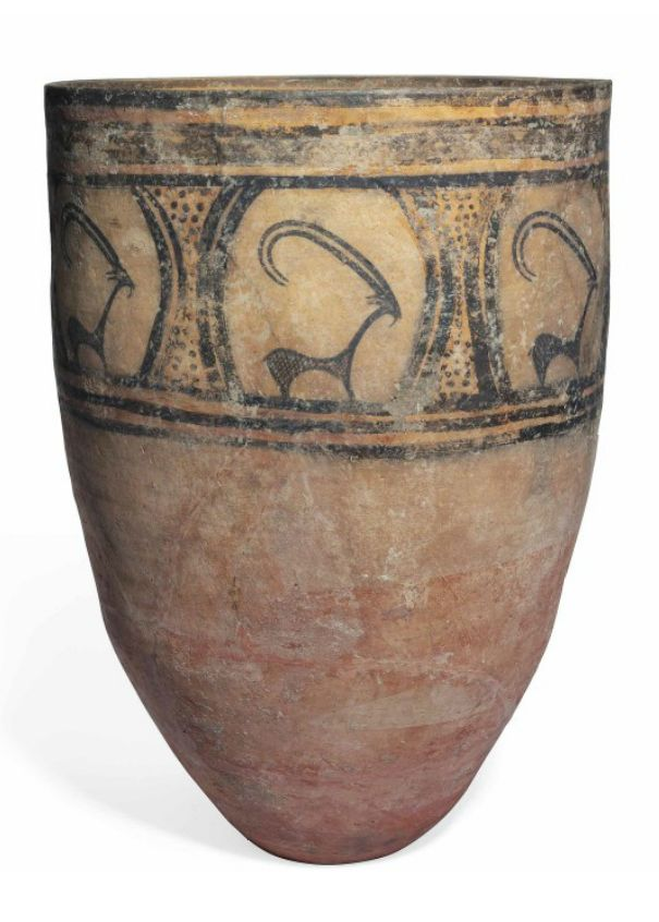 A LARGE PERSIAN POTTERY JAR CIRCA 3000 BCE. The cylindrical body tapering towards the foot, decorated in dark brown with seven roundels enclosing a stylized ibex with cross-hatched body, thin beard and long backward-curling horns, waisted columns of stippled decoration between, horizontal bands above and below 23 5/8 in. (60 cm.) high