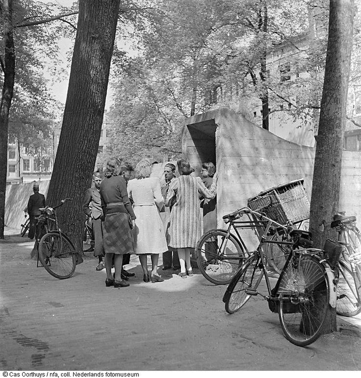Inwoners staan bij de ingang van een schuilkelder, mogelijk op de Herengracht, Amsterdam (1940)