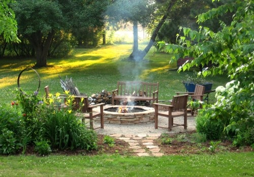 Fire pit. Gravel with chairs and benches.