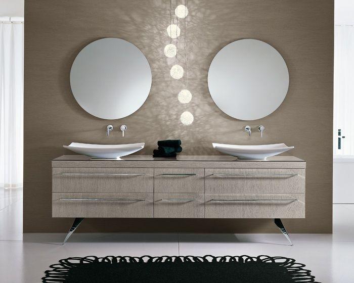 en este baño están dos lavabos con dos grifos y dos espejos.debajos de dos lavabos hay un mueble con seis cajónes.