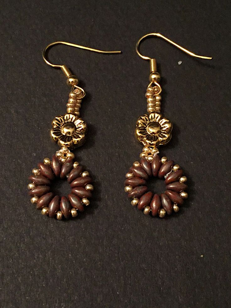 These Brown super duo drop handcrafted earrings are perfect to wear any occasion. Materials: - Brown Picasso super duo beads - gold seed beads - gold flower - gold hook Measure: - 2 1/2 inch