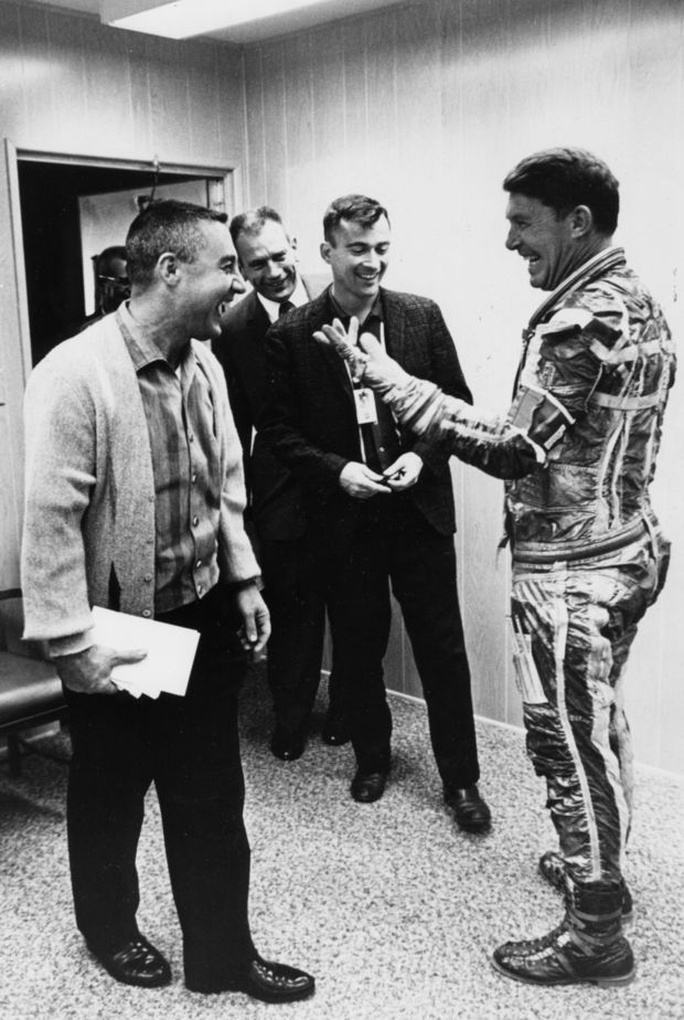 "Astronauts ""Gus"" Grissom, ""Deke"" Slayton and John Young ((left to right), get a kick out of Wally Schirra clowning in an old fashioned space suit liner."