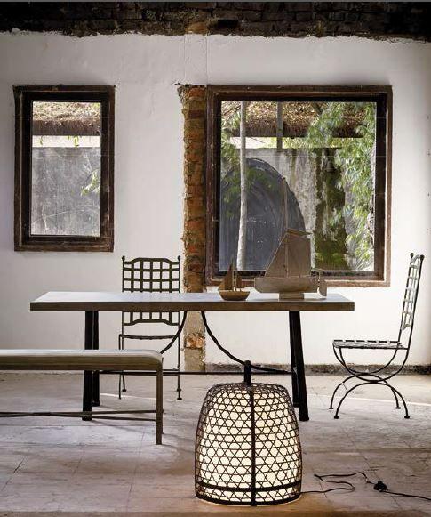 Memorias de África Este comedor está compuesto por una mesa de hierro con detalles de taches en los laterales, sillas de jardín en rejilla verde óxido y una banqueta tapizada en tela.