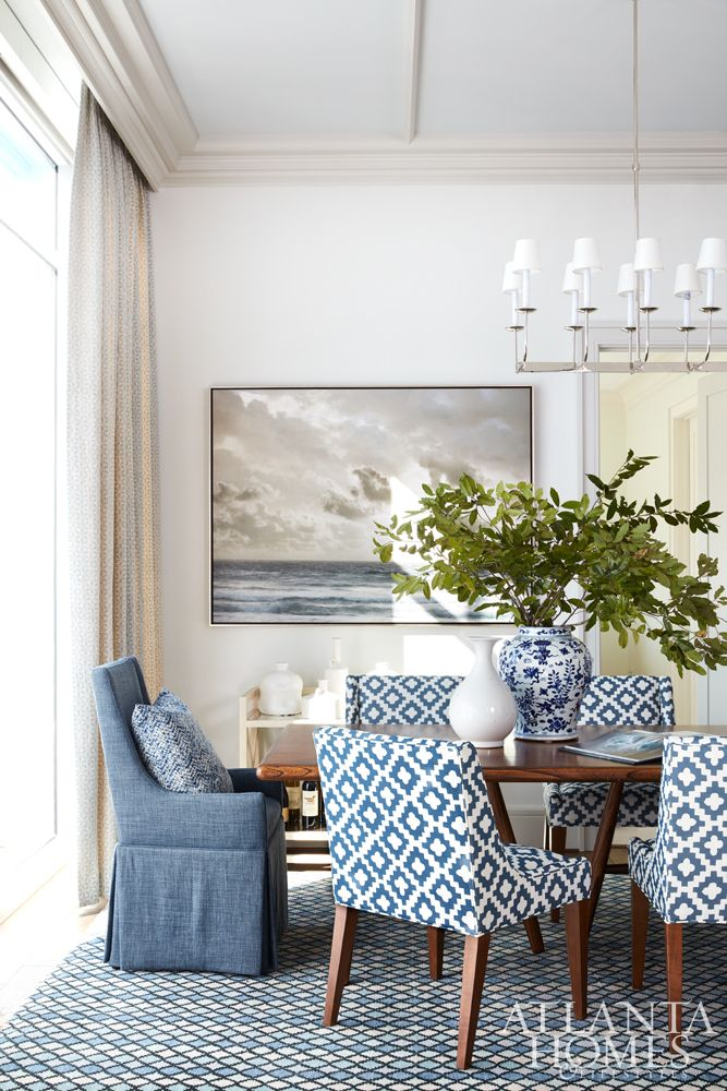 The custom rug in the dining room has seven shades of blue that Andrew Howard continued throughout the condo. The seascape painting is a reminder of the owner's hometown of Jacksonville, Florida, and is from Mrs. Howard in Atlanta. Side chairs, Mitchell Gold   Bob Williams in Peter Dunham.