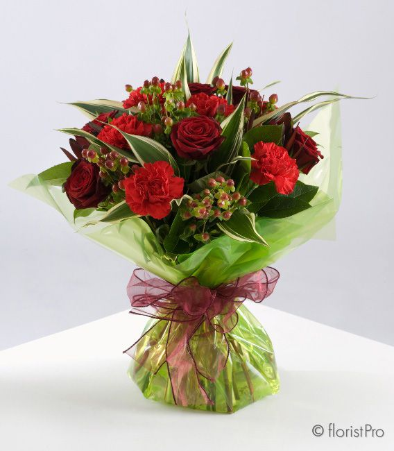A beautiful handtied bouquet, elegantly wrapped containing a mixture of roses, carnations and foliage.