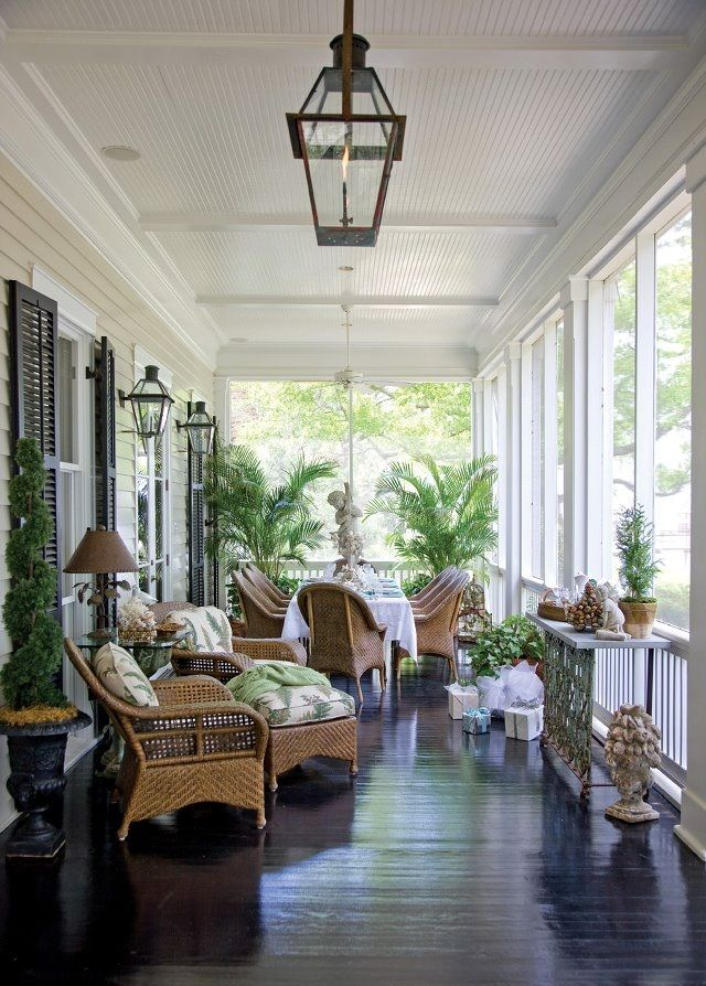 The dark stained porch floor makes everything pop. A beautiful arrangement of furniture and accessories.