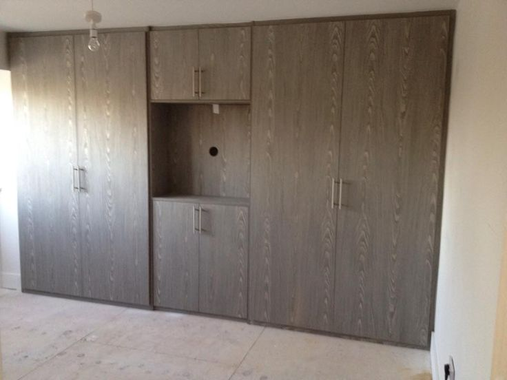 French grey fitted hinged wardrobe made to measure with centre opening for tv. Below is a link to our online calculator to see how much your bespoke made to measure wardrobe will cost http://www.foxwardrobes.co.uk/instant-online-estimator/