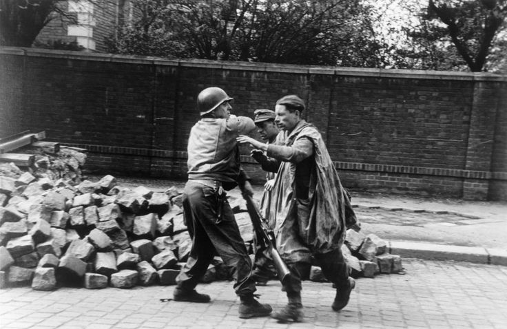 Robert Capa - Leipzig. April 18th, 1945. An American soldier captures German soldiers.