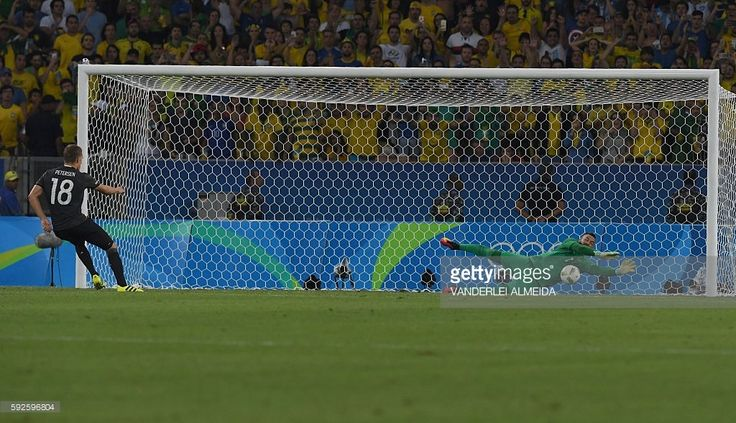 Brazil's goalkeeper Weverton Pereira da Silva (R) dives to save a penalty shot…