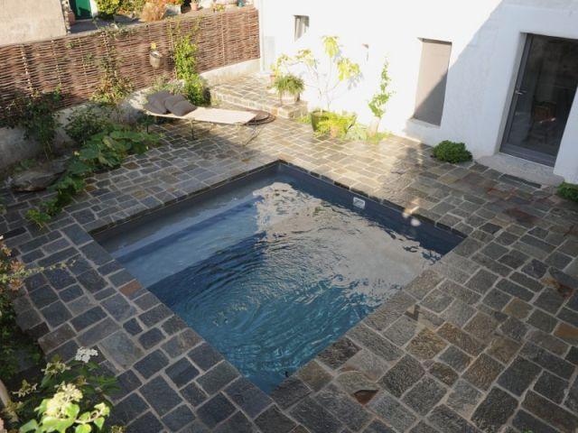Petite piscine dans une cour intérieur avec abords en pierre
