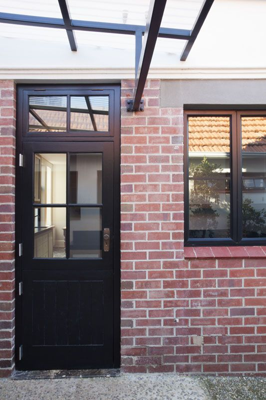 Black painted timber stable door with aluminium window by Victoria de la Cour- architect