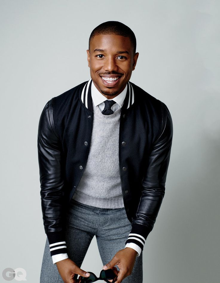 Shop this look on Lookastic: https://lookastic.com/men/looks/varsity-jacket-crew-neck-sweater-dress-shirt/15774   — White Dress Shirt  — Black Knit Tie  — Grey Crew-neck Sweater  — Black Varsity Jacket  — Grey Wool Dress Pants