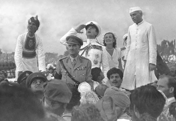 Lord Mountbatten salutes India's national flag as his wife, Edwina, and the Indian prime minister, Jawaharlal Nehru, look on. Credit: AP