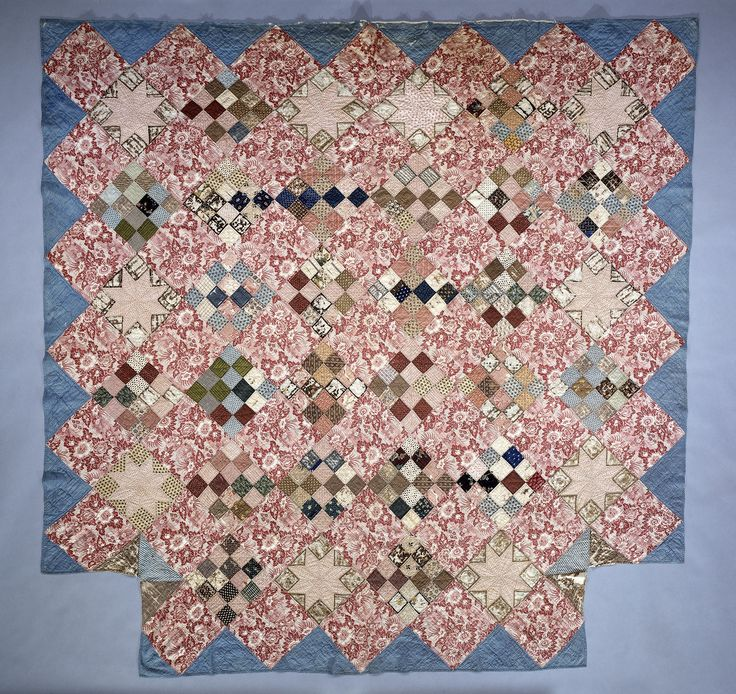 """This quilt, made between 1825 and 1850, was found in a house in Londonderry, VT.   Ten-inch blocks of red-and-white floral printed fabric alternate with """"Sixteen-Patch"""" blocks composed of many block- and roller-printed fabrics. Ten """"Eight-pointed Star"""" blocks of block-printed red-and-white fabric are set near the outer edge. Three quilting patterns are utilized for the three different types of blocks, quilted 6-7 stitches per inch."""