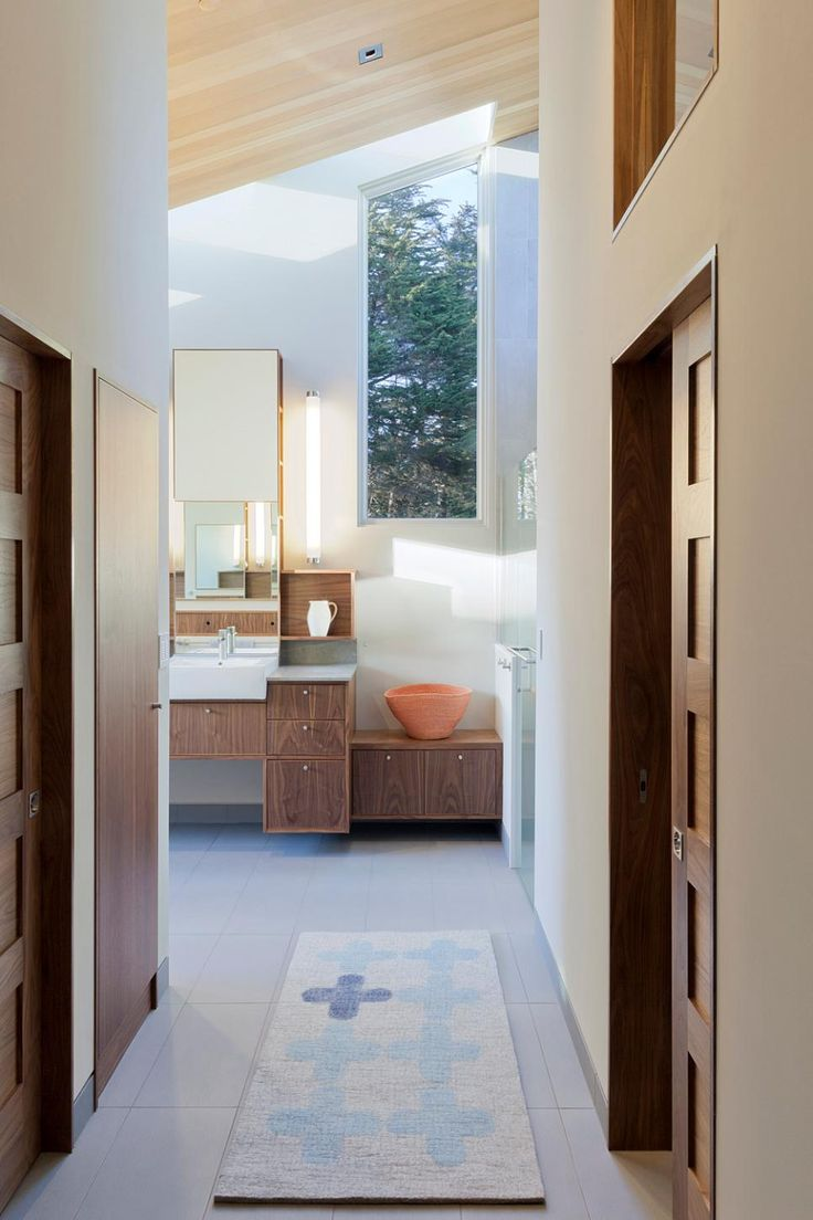 Stark white walls and light wood ceiling make this master bathroom design feel bright and airy. An angled, rectangular window fills the space with natural light.