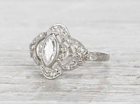 Antique Edwardian engagement ring made in platinum and centered with a .31 carat marquise cut diamond. Accented with single cut diamonds. Circa 1915.