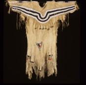 Zwartvoet Indianen zijn van oorsprong jagers. Voor hun kleding en gebruiksvoorwerpen maken ze gebruik van materialen die voorhanden zijn. Deze jurk is gemaakt van leer. Het is een kledingstuk voor dagelijks gebruik. De jurk is versierd met kralen, franjes en belletjes. Oorspronkelijk is de jurk waarschijnlijk ook met hermelijnbont gedecoreerd geweest, maar hiervan zijn geen resten meer over. Met de komst van Europese kolonisten komt vanaf de 19e eeuw ook westerse kleding beschikbaar voor de…