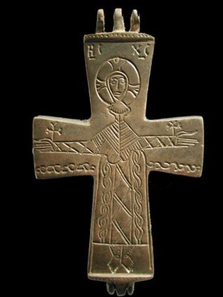 Ornately incised Reliquary cross depicting a crucified Christ with small crosses place where nails pierced his outstretched arms
