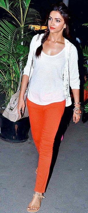 On trend: Deepika Padukone pairs a simple white top and cardigan with vibrant, bright-orange jeans