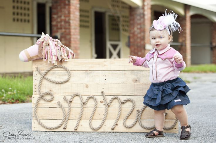 Emma's one year photoshoot by CindyFarache.com - cowgirl party outfit (western onesie, denim skirt, brown sandals/StrideRite, mini cowgirl hat Etsy) Sign made by her dad and horse head on a stick made by her grandmother Ayla @ diapercakesalacarte, mini cowgirl hat by Christy Wilson on Etsy
