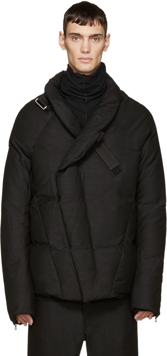 Long sleeve down jacket in black. Subtle slub effect throughout. Stand collar. Grosgrain strap wraps around collar and fastens at front. Offset zip closure at front concealed by press-stud placket. Zip pockets at waist. Zippered vent at sleeve cuffs. Fully lined. Tonal stitching.
