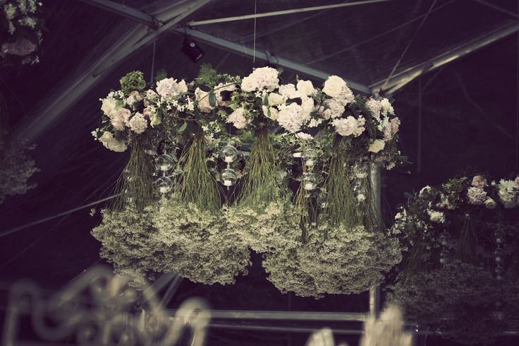 chandelier covered with greenery and soft colors flower, plus hanging boules with candles