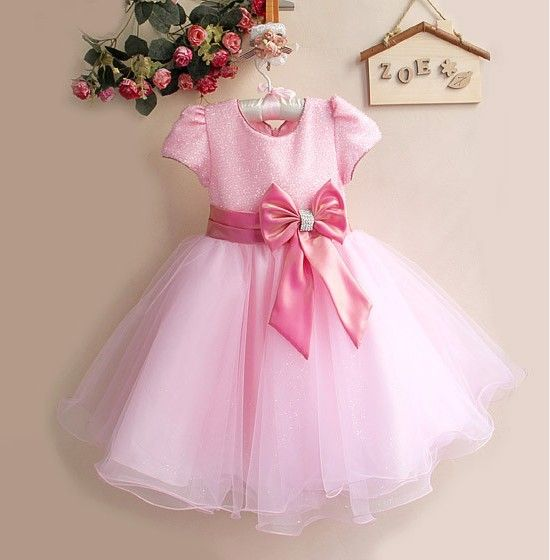 Buy online in India the fashionable little princess dress in pink. The combination of shimmery bodice with puffed sleeves and shiny net flare with a big bow and diamond embellishment makes it an ideal baby wedding dress for your infant.