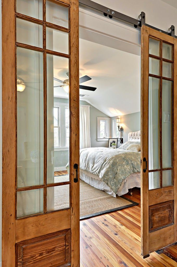 Curtains on one side of this fabulous pair of sliding barn doors with divided-light glass-tops can be closed for added privacy.