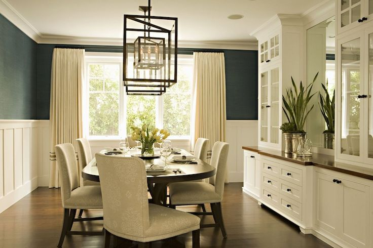 Elegant dining room with teal blue grasscloth wallpaper, board and batten walls, ivory curtains window panels, iron lanterns and glass-front built-in buffet